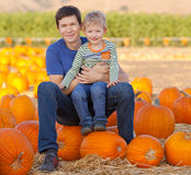 Family at the pumpkin patch. Family of father and son spending fun time together at the pumpkin patch Stock Photos