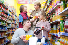 Family purchasing carbonated beverages. Happy young family of customers with children purchasing carbonated beverages Royalty Free Stock Images