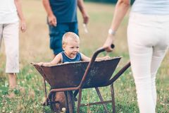 Family pushing their small child in a wheelbarrow. Family pushing their small child and grandchild in a wheelbarrow royalty free stock image