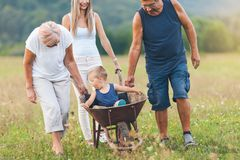 Family pushing their small child in a wheelbarrow. Family pushing their small child and grandchild in a wheelbarrow stock photo