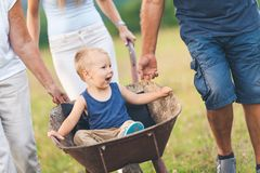 Family pushing their small child in a wheelbarrow. Family pushing their small child and grandchild in a wheelbarrow royalty free stock images