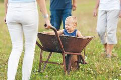 Family pushing their small child in a wheelbarrow. Family pushing their small child and grandchild in a wheelbarrow stock photography