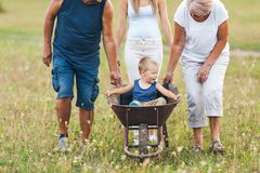 Family pushing their small child in a wheelbarrow. Family pushing their small child and grandchild in a wheelbarrow stock photos