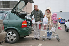 Family puting shopping bags in car. Family with baby puting shop bags in car stock photos
