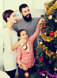 Family putting decorations on Christmas tree royalty free stock photos