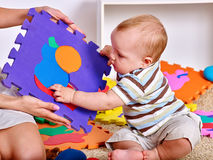 Family puzzle making mother and baby. Child jigsaw develops children. Royalty Free Stock Images