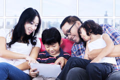Family quality time using touchpad at apartment Stock Photography