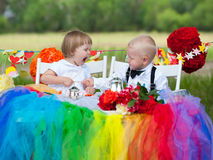 Family quarrel. Baby girl shouts at baby boy (both are dressed as groom and bride Royalty Free Stock Images