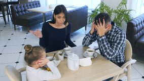 Family quarrel in cafe. Mother is very nervous scolding on daughter and husband. stock photos