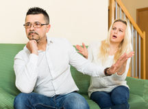 Family quarrel at home. Family quarrel. Sad guy and his young angry wife during quarrel in living room at home stock photo