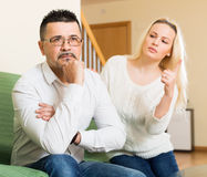 Family quarrel at home. Family quarrel. Sad men and his angry young blonde wife during quarrel in living room at home Royalty Free Stock Photos