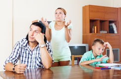 Family quarrel. Ordinary family of three with teenager boy having quarrel in living room stock photography