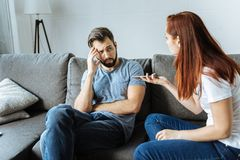 Unhappy angry woman talking to her boyfriend. Family quarrel. Unhappy angry young women looking at her boyfriend and talking to him while holding his smartphone Royalty Free Stock Photo