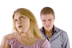 Family quarrel. white background. Young couple quarrel. A man in a rage, the woman is indifferent Royalty Free Stock Photo