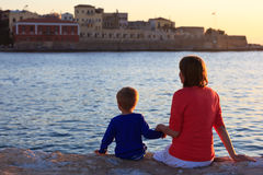 Family on the quay of Crete at sunset Royalty Free Stock Photography