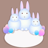Family of rabbits and Easter eggs. Three white rabbit, easter eggs, place for text Royalty Free Stock Images
