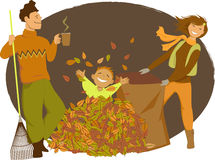 Family raking autumn leaves Stock Photo