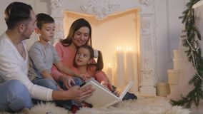 Family read book sitting on sofa in front of fireplace in Christmas decorated house interior stock footage