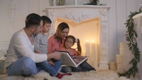 Family read book sitting on sofa in front of fireplace in Christmas decorated house interior stock video