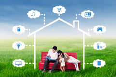 Family read book under an illustration of smart house. Portrait of happy family sitting on the sofa while reading a book under an illustration of smart house at Royalty Free Stock Photos