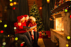 Family read stories sitting on coach in front of fireplace in Christmas decorated house interior. Family read stories sitting on sofa in front of fireplace in stock photo