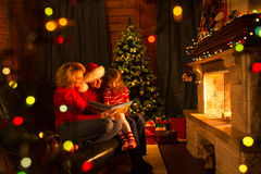 Family read stories sitting on sofa in front of fireplace in Christmas decorated house interior Royalty Free Stock Photos