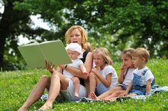 Family readind a book outdoors Stock Photos