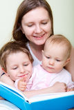 Family reading. Young mother with her two kids reading book in bed royalty free stock photos