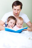 Family reading. Young father and two kids reading book in bed stock photography