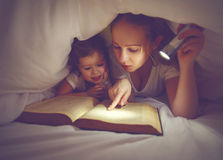 Family reading bedtime. Mom and child reading book with a flashl Stock Image
