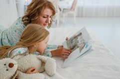 Family reading bedtime. Pretty young mother reading a book to her daughter. Mother reads a fairy tale to her daughter. A royalty free stock photos