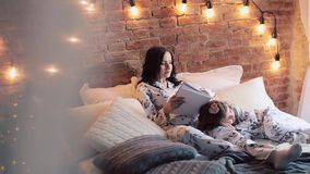 Family reading bedtime. Pretty young mother reading a book to her daughters. stock footage