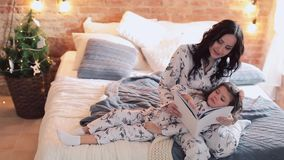Family reading bedtime. Pretty young mother reading a book to her daughters. stock video