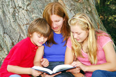 Family reading a book Royalty Free Stock Photo