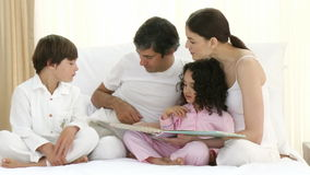 Family reading a book on bed Stock Image