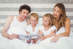Family reading book on bed Stock Image
