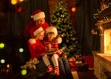 Family reading a book by a Christmas tree in cozy Stock Photos