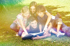 Family reading  book in garden in summer. Happy family reading a book in garden in summer Stock Photography