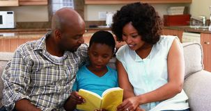 Family reading a book in living room 4k. Family reading a book in living room at home 4k stock video footage
