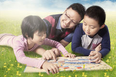 Family reading book while lying on meadow Royalty Free Stock Photo