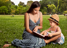 Family reading a book in the park Royalty Free Stock Photo