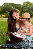 Family reading a book in the park Royalty Free Stock Photos