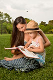 Family reading a book in the park Stock Photo