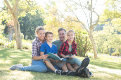 Family reading a book in the park on a sunny day Royalty Free Stock Photo