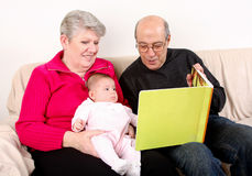 Family reading book to baby. Happy fun Caucasian Hispanic Middle Eastern family sitting together on couch reading book to baby. Grandfather and Grandmother royalty free stock photo