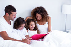 Family reading book together on bed Stock Photography