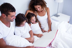 Family reading book together on bed Stock Image