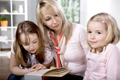 Family at reading in the flat Royalty Free Stock Images