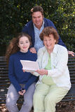 Family Reading Good News. A father, daughter and grandmother reading good news together Stock Photos
