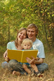 Family reading in nature. Happy young family reading book in nature Royalty Free Stock Photography